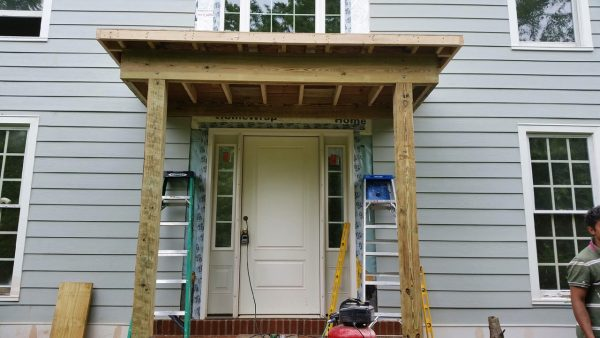 Portico Addition Over Front Door Of Large Grey Home During Construction